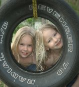 Children playing on tire swing
